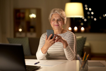 technology, old age and communication concept - happy senior woman with smartphone and papers at home in evening