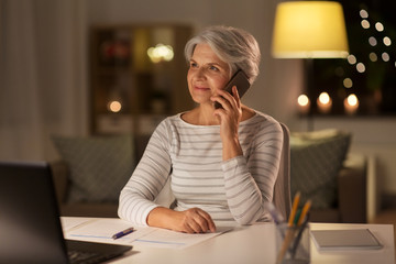 technology, old age and communication concept - senior woman with laptop computer and papers calling on smartphone at home in evening