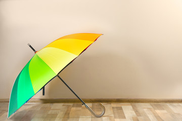 Wall Mural - Beautiful open colorful umbrella near beige wall. Space for text