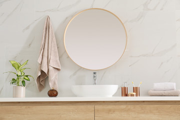 Round mirror over vessel sink in stylish bathroom interior
