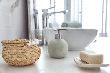 Soap bar and cotton swabs on table in bathroom