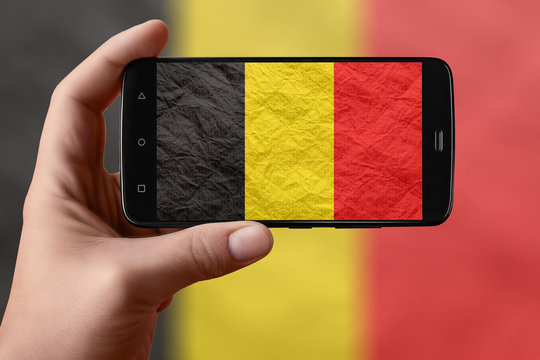 Belgium flag on the phone screen. Smartphone in hand photographing flag.