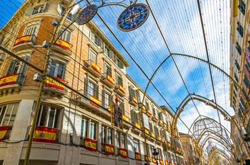 Buildings on Calle Marques de Larios street in the centre of Malaga city decorated with Spain flags and Christmas lights. Most popular pedestrian street of Malaga, Andalusia, Spain