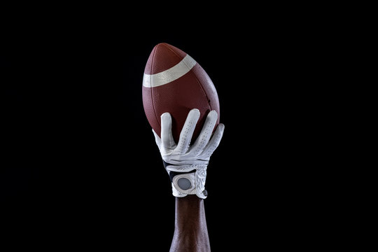 Hand of a player holding American football