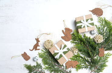 Australia inspired rustic Christmas flat-lay featuring native Australian mammals amongst Christmas foliage and gifts on a white background.