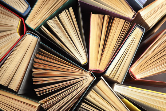 Many different hardcover books on dark background, top view