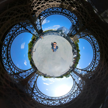 Little planet 360 degree sphere. Panoramic view of a tourist in the base of the Eiffel tower
