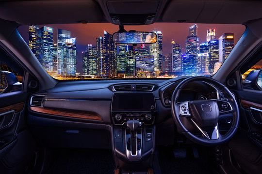 Looking through a car windshield with cityscape at night. Travel in car.