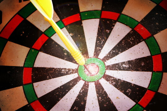 Yellow darts arrow hit in the target center of old dartboard. Concept mission complete after try many time.