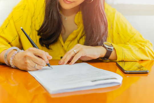 Businesswoman signing contract document paper on wood table.