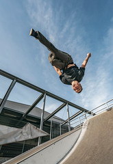 Young Parkour and Freerunning athlet doing a backflip from a wall in an urban enviroment with a blue sky in de background, jumping tumbling  Gymnastics training concept