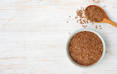 Flax seeds in wooden spoon and bowl on vintage background