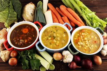 Set of soups from worldwide cuisines, healthy food. Broth with noodles, beef soup and broth with marrow dumplings. All soups with healthy vegetables on table