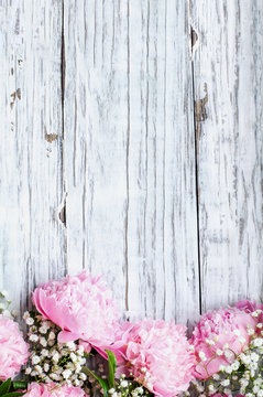 Bouquet of pink Peonies and Baby's Breath flowers over a white rustic wood table background  with copy space for your text. Flat lay.
