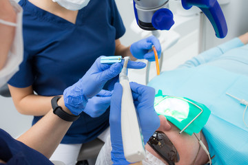 Close-up picture of dental instruments: drill and needle for root canal treatment and pulpitis in hand at the dentist in a blue glove