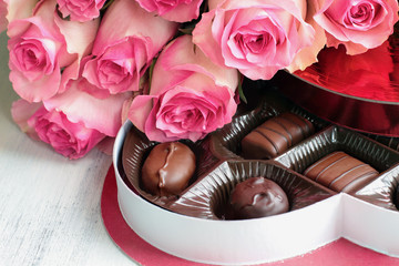 Dozen soft colored long stem pink rose flowers with a heart shaped box of chocolate candy for Valentine Day over a wood background.