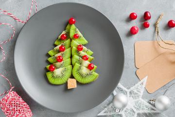 Kiwi Christmas tree with currants, funny food for kids. Christmas food background.