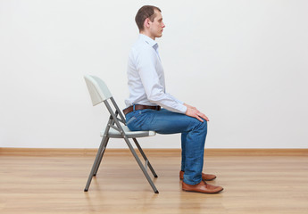 caucasian man sitting on the edge of chair in correct  posture Wall mural