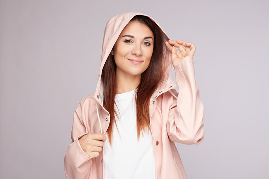 Close up shot of attractive young female tourist wears hood, being wet after walking at rainy weather, looks with appealing dark eyes directly into camera, touching hair. Young traveller being glad.