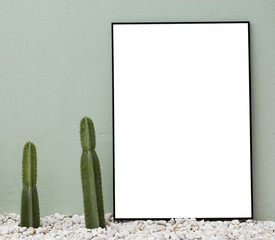 Pair of two cacti in stone gravel pebbles adjacent next to plain empty blank black thin narrow rectangular photo picture frame with white copy space leaning resting against on rough green painted wall