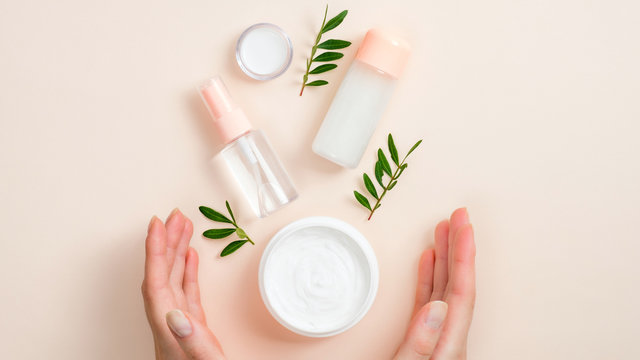Jar of organic hand cream, essential oils bottle and green leaves on beige background. Skin care, organic natural beauty products concept