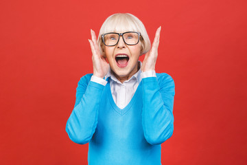 Old adult blonde glad excited cheerful astonished lady smiling, laughing, screaming, raising hands to cheeks, opened mouth, isolated over red background.