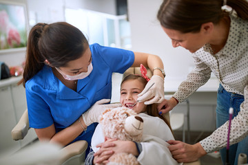 Little girl visiting dentist .Dentist examining tooth patient in ambulant.