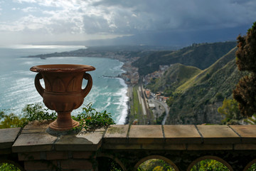 clay vase with view in the background of Giardini Naxos seen from Taormina, Sicily, Italy