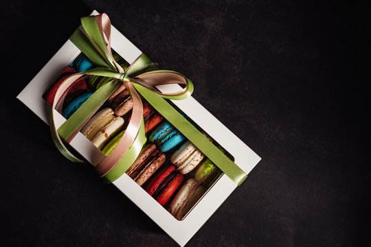box with macaroon cakes on a black background, tasty gift