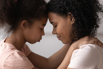 Side view mother and daughter touches foreheads moment of tenderness