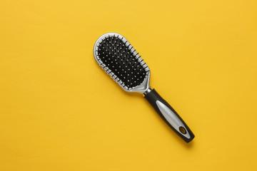 Stylish hairbrush on yellow background. Women's Hair Care Accessories.