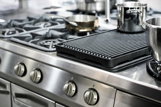 Part of a modern kitchen in the restaurant or hotel with professional equipments - steel gas cooker, pots and pans ( low DOF)