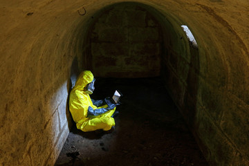 Man in protective uniform, gas mask,gloves, boots watching pictures  in dark tight shelter