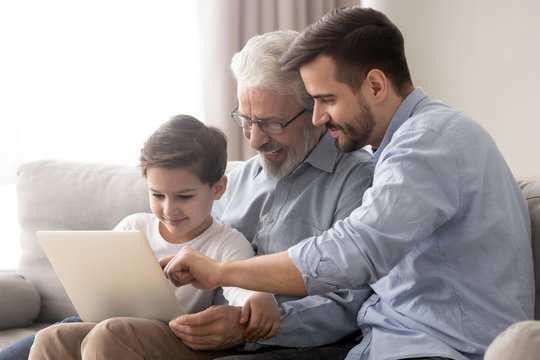 Happy grandfather and father teaching little boy to use laptop