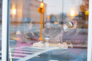 Mother and daughters sitting in cafe drinking coffee and taking. have conversation, happy and sad.  Picture through window.