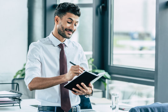 young businessman smiling while writing in notebook
