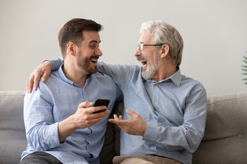 Happy old father and son having fun, using phone together