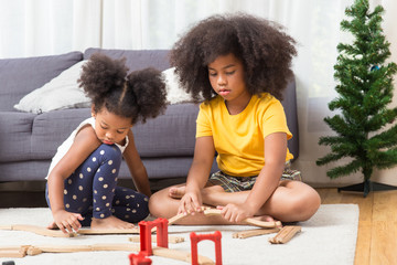 two black girl daughter kids playing train model together at living room.