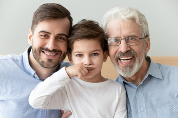 Head shot portrait smiling grandfather, father and preschool son