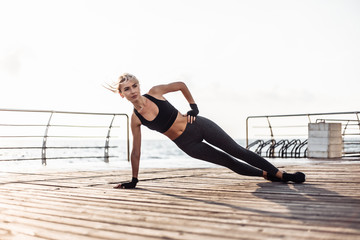 Deurstickers Ontspanning Healthy woman training on seaside promenade. Young sport woman in sportswear doing side plank exercise on the beach at sunrise