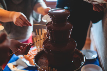 Vibrant Picture of Chocolate Fountain Fontain on a children kids birthday party with a kids playing around and dipping marshmallows and fruits into the fountain