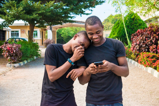 two young black men walking and holding each other laughing together while viewing content on a mobile phone. gay couple laughing together while using a phone together