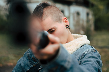 Young woman with short hair and a punk style, holds an old double-barrel shotgun in an abandoned estate. She is pointing at the camera.
