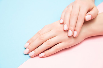 Beautiful female hands with stylish nail manicure gel polish on pink and blue background, top view. Skin care concept