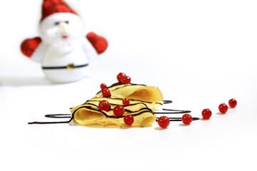 Fototapeta Naleśnik w kształcie choinki z pożeczkami, czekoladą i mikołajem w tle. obraz