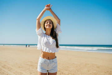 joyful tourist in a straw hat stretching on a deserted beach by the ocean