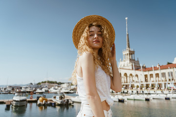 curly blonde looks down at the camera on the background of the sea and boats