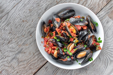 Steamed Mediterranean Seafood dish of Mussels with tomatoes and green onions flat lay