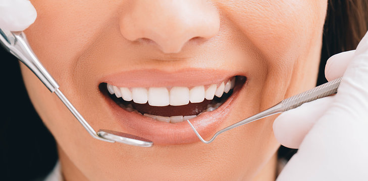 Cropped perfect smile and dentist hands holding a dental equipment and an angle mirror. Dentistry and teeth treatment