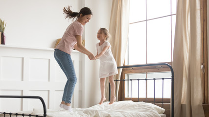 Playful mom have fun jumping on bed with little daughter